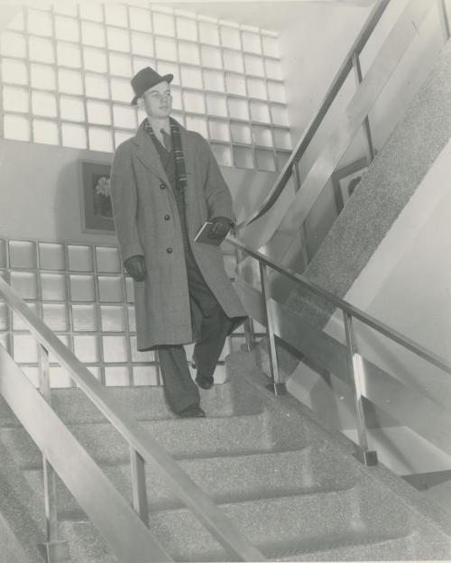 A well-dressed young man heads to class from Seerley Hall