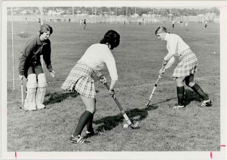 Women playing field hockey, 1975