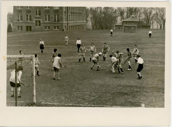 Women playing field hockey, 1930