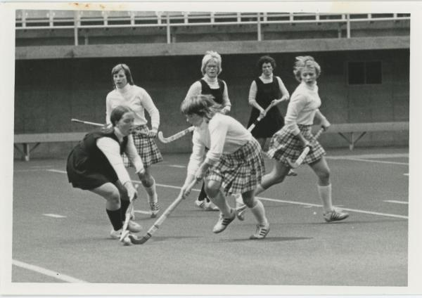 Women playing field hockey in the UNI dome, 1976