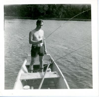 Eugene Francis Grossman fishing while standing inside of a fishing boat. Eugene Francis Grossman photograph, in the Eugene Francis Grossman Papers 1896-1965, #MsC-38, photographs of family and friends, box 1, University of Northern Iowa.