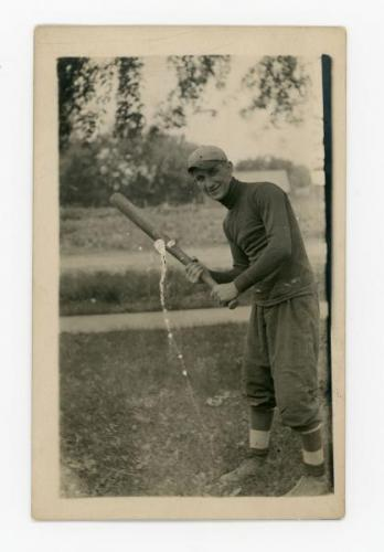 Eugene Grossman posing with a baseball bat.