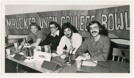 Four men sitting at a table in front of a Maucker Union College Bowl banner.