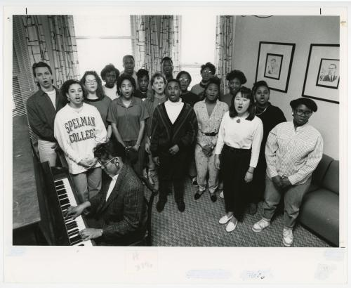 A group of singers singing while a man plays the keyboard.